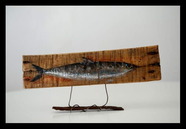 Ecological Artwork like this sardine-themed wall art piece are made with upcycled materials, such as pallet wood, rebar, wire and more.