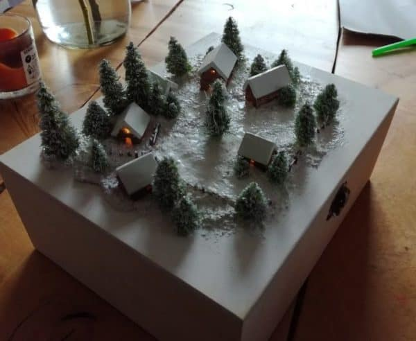 This little Winter Model Village is a fun upcycling project. the little cabins are sided with toothpicks to imitate log sides.