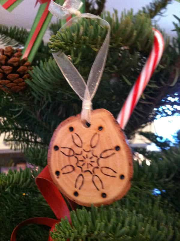 DIY Christmas Decorations can be fun to make, like this woodburned wood slice from a branch or trunk of a tree.