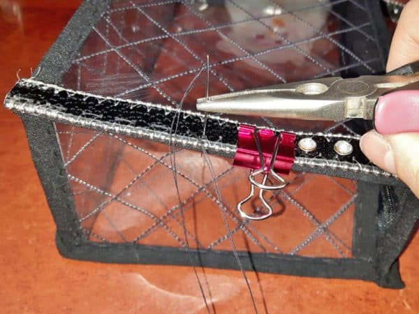 Hand-stitch the strap, sides, and more together using clamps and pliers for the Upcycled Plastic Bottle Handbag.