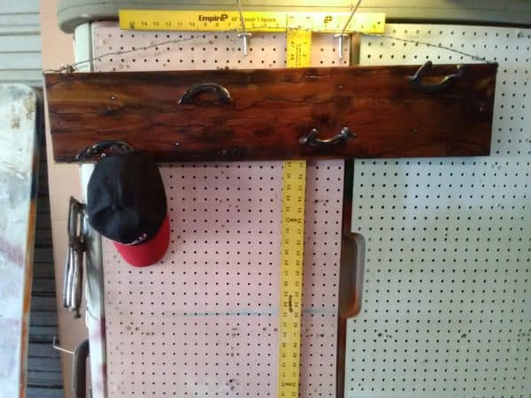 Upcycle a cedar board and don't bother filling the cracks or fissures. It'll make this Horseshoe Hat Rack look more rustic and stunning.
